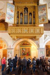 Chiesa di San Nicola, visita guidata davanti alla tavola dell'Annunciazione. In alto, il monumentale organo Antegnati del 1588